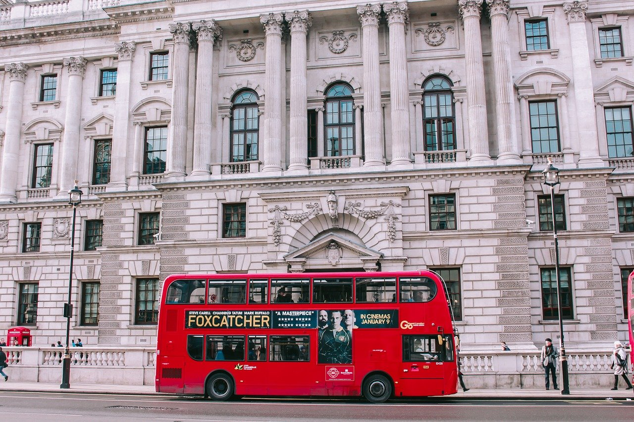 Red double decker bus driving down the street in London, England. A large concrete building with Roman-like columns is in the background