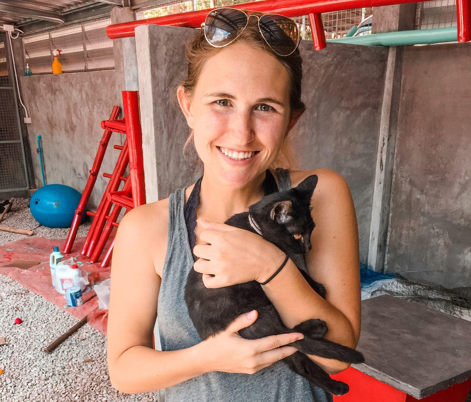 Hannah Corderman holding a small black cat at an animal shelter in Ko Lanta Thailand