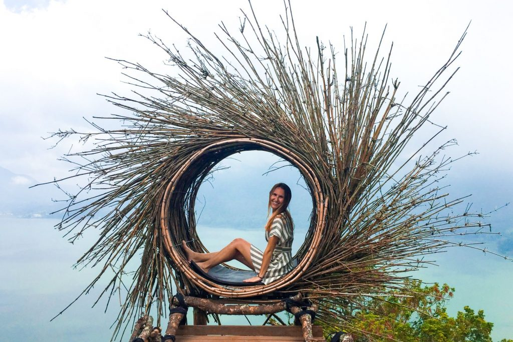 Hannah Corderman sitting on manmade nest overlooking lake in Bali - We Are Travel Girls - Wanderlight Moments - Travel Blogger