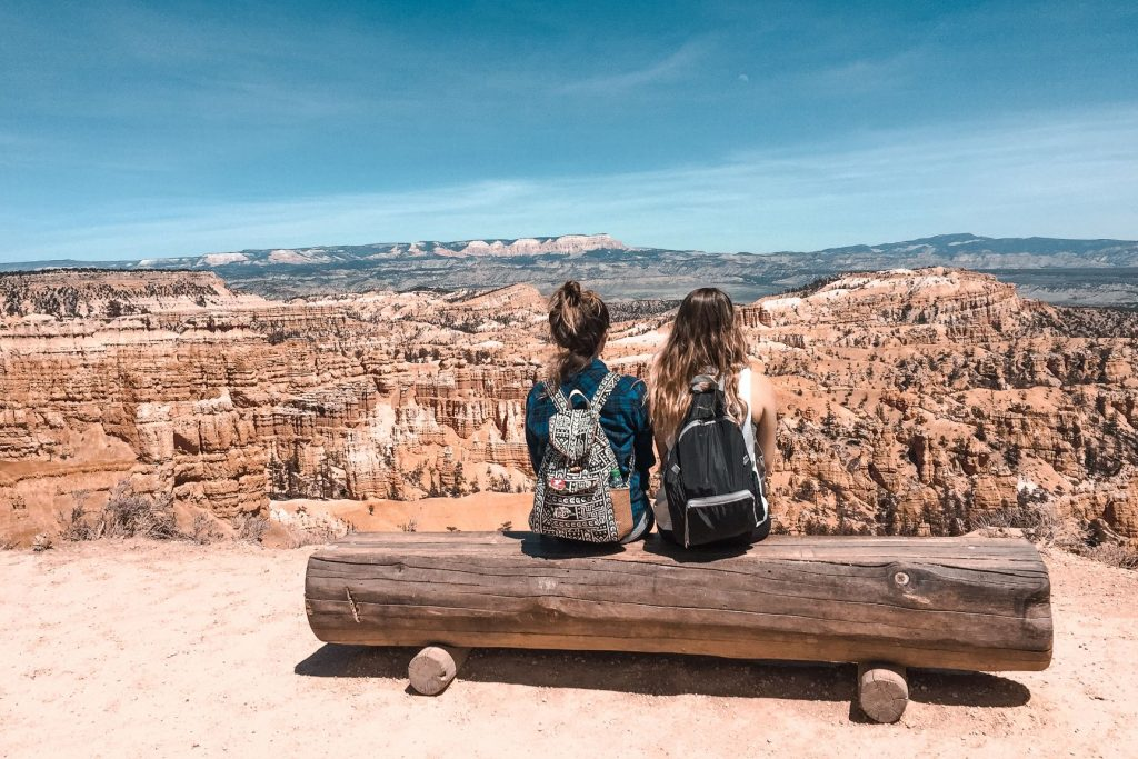 Hannah Corderman and friend both wearing backpacks while sitting on a wooden bench looking out at Bryce Canyon National Park in Utah