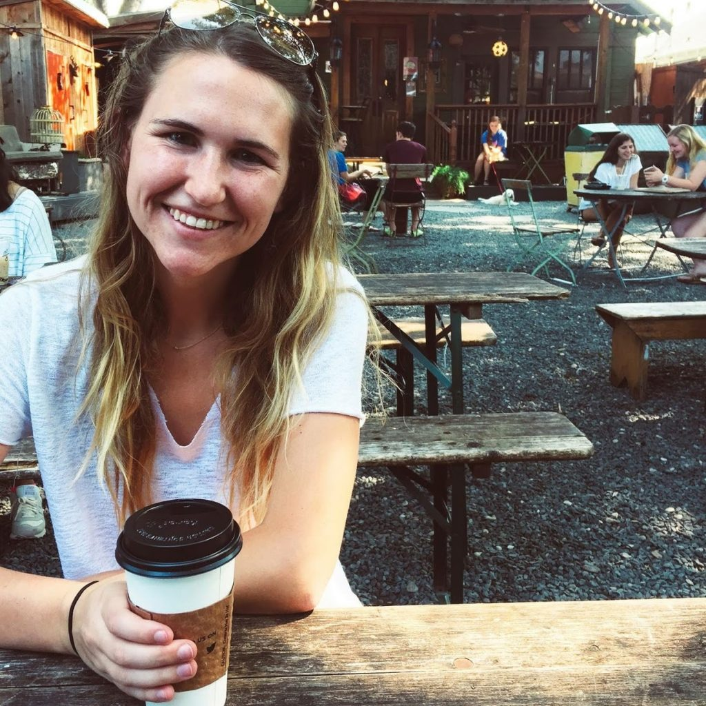 Hannah Corderman sitting at a picnic table in Waco Texas holding a hot coffee in her hand - Wanderlight Moments - Travel Blogger