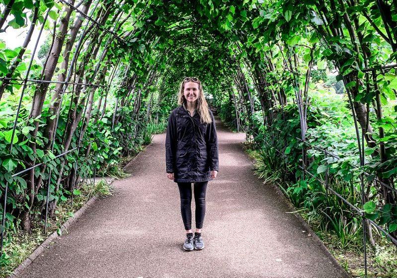 Hannah Corderman standing in Kensington Gardens surrounded by greenery