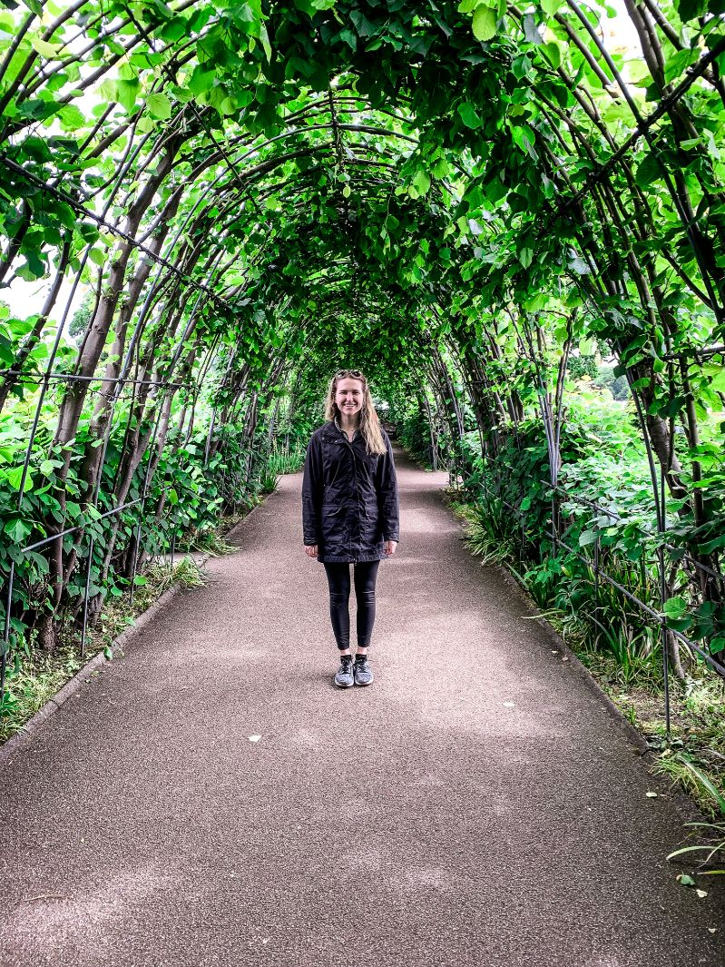 Hannah Corderman standing in Kensington Gardens surrounded by greenery