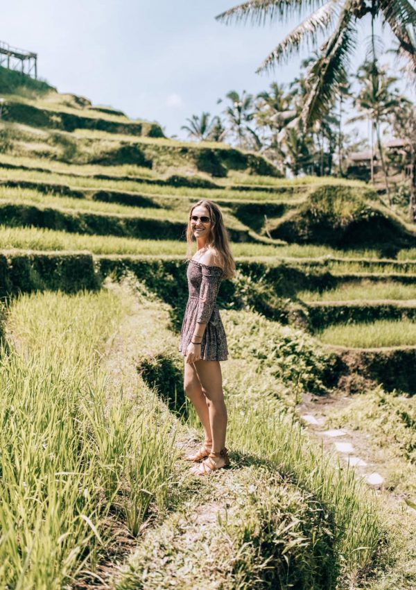 Hannah standing in a rice patty in Bali - We Are Travel Girls