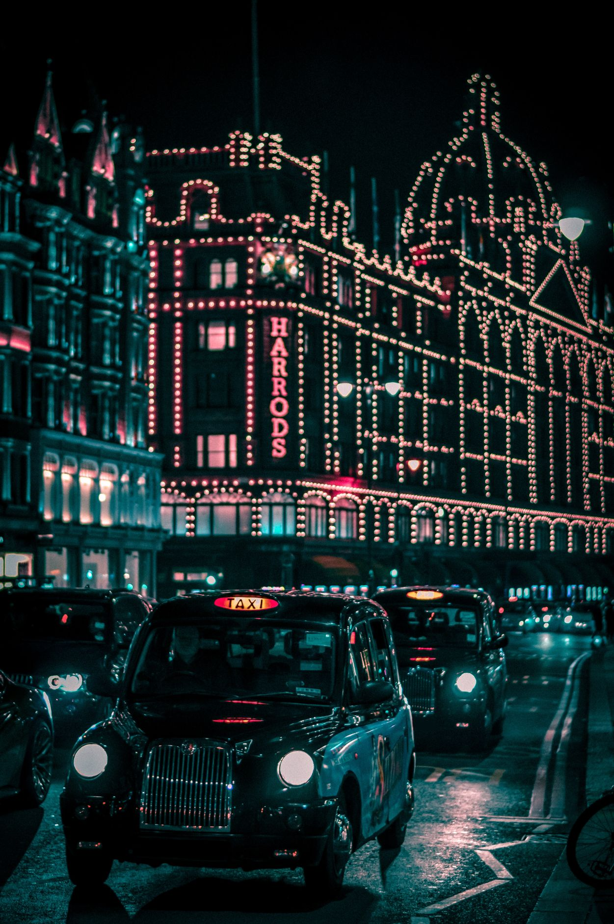 Taxis driving by Harrod's department store in London, England at night. Harrod's is lit up with decorative lights