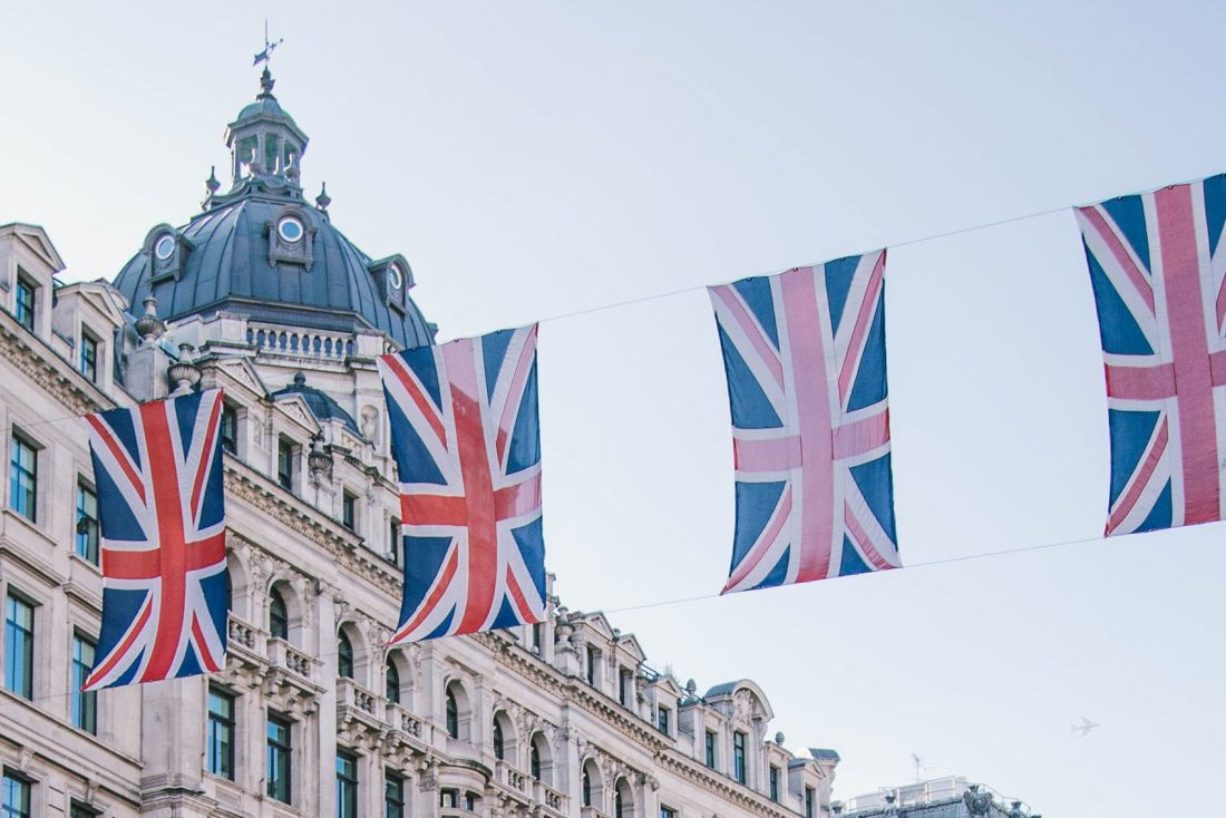 british flags hanging in London with buildings in the background - bucket list travel