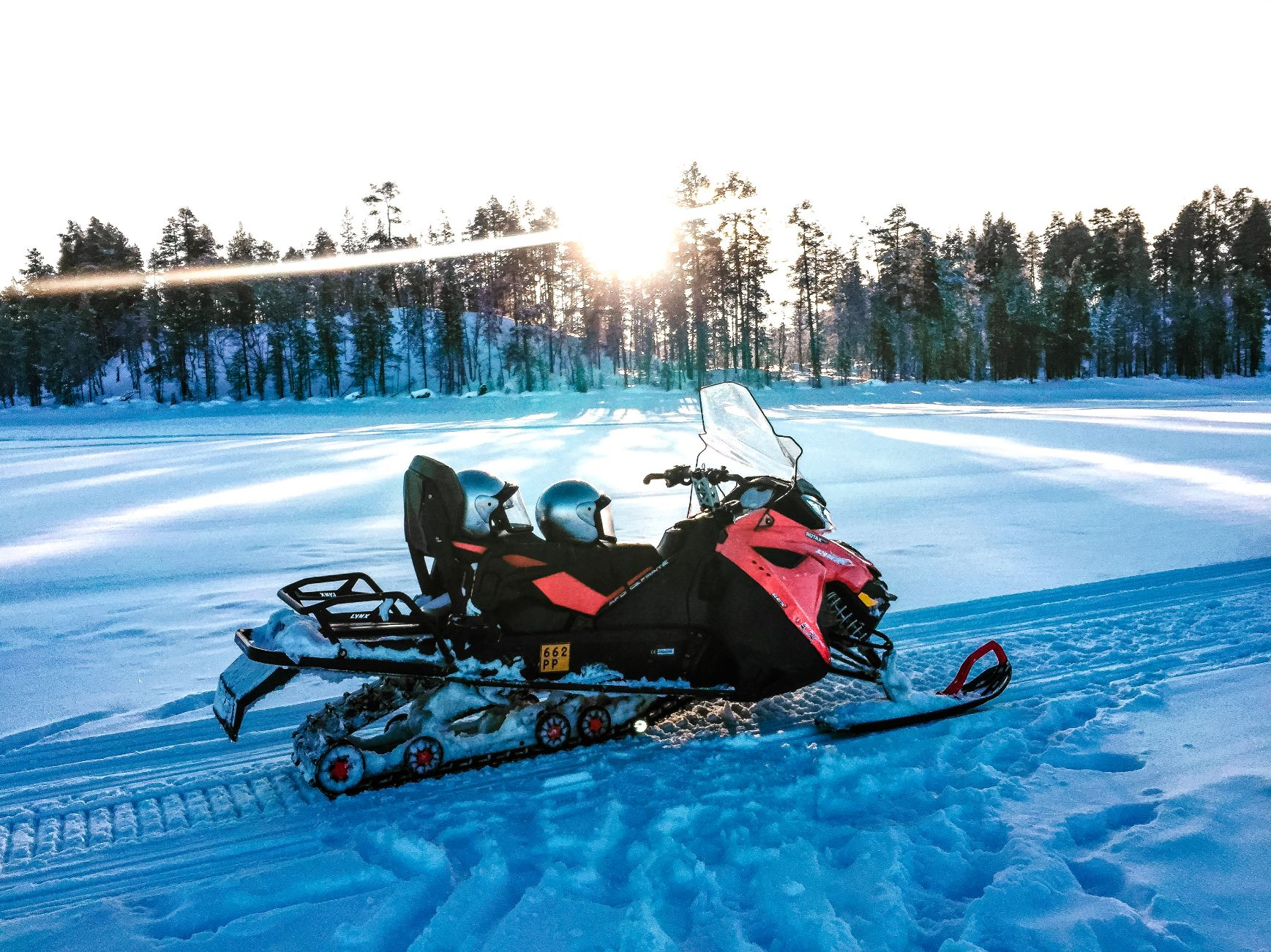 snowmobile on frozen lake with sun shining through trees in the background in Finnish Lapland