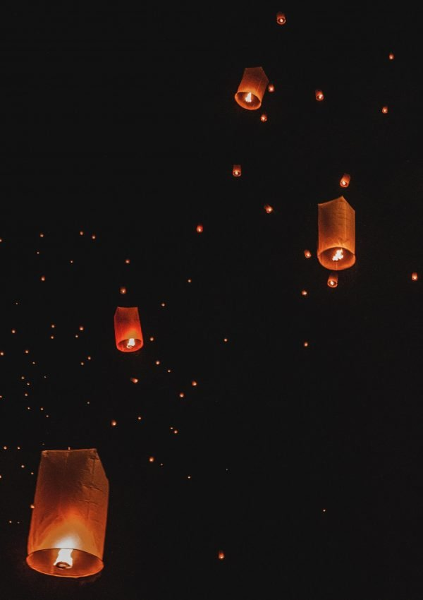 Lanterns floating in dark night sky in Chiang Mai Thailand during lantern festival