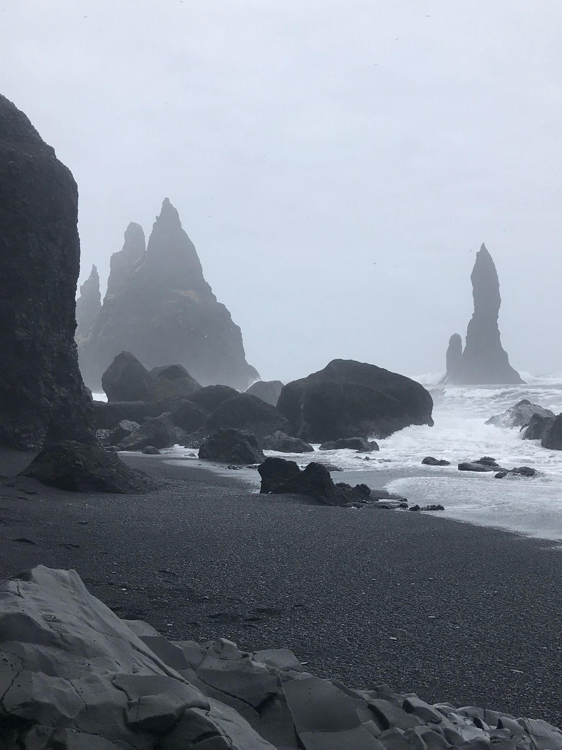 Black sand beach with lava rock formations coming out of winter ocean in Iceland - stop in 24 hour Iceland itinerary
