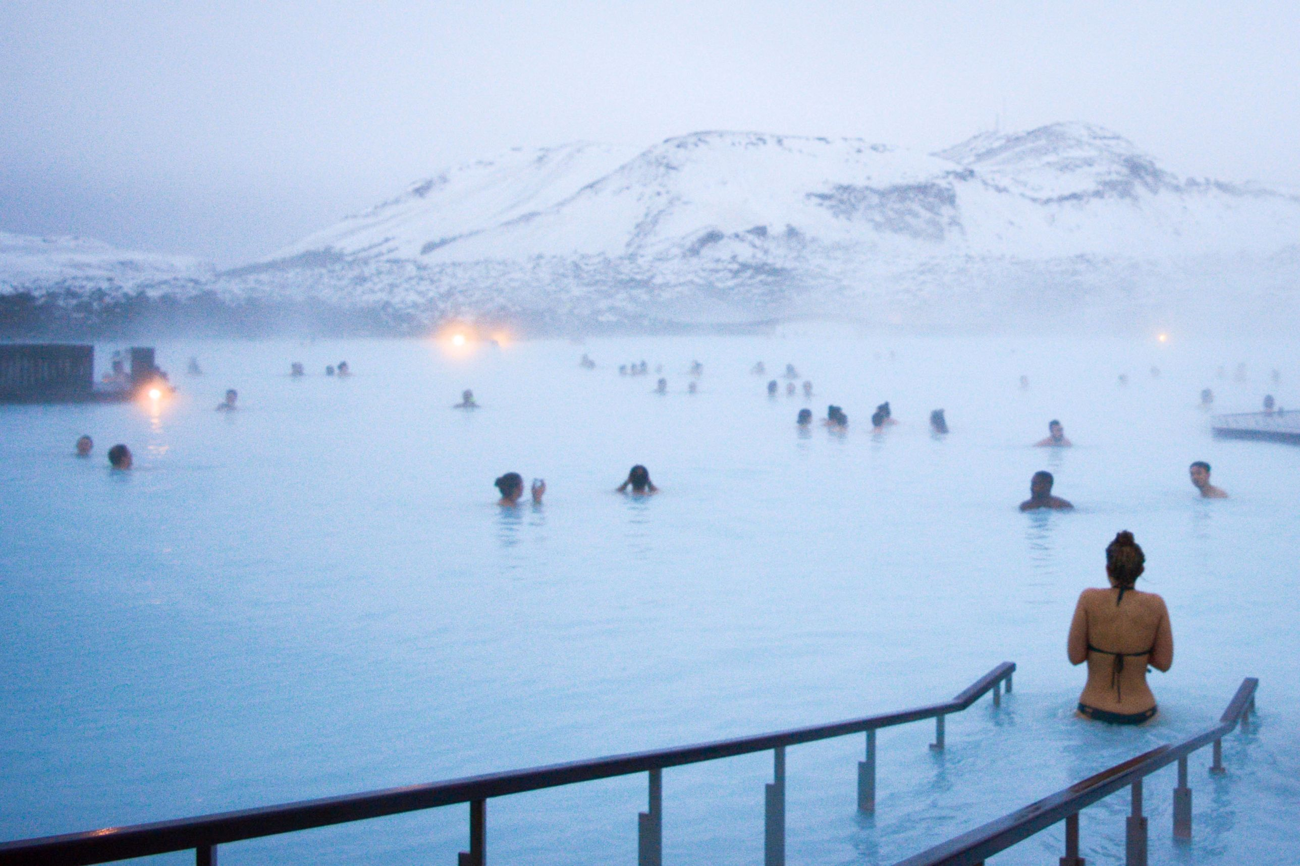 Girl walking into the blue lagoon with lots of people relaxing in the water in Iceland - stop in 24 hour Iceland itinerary