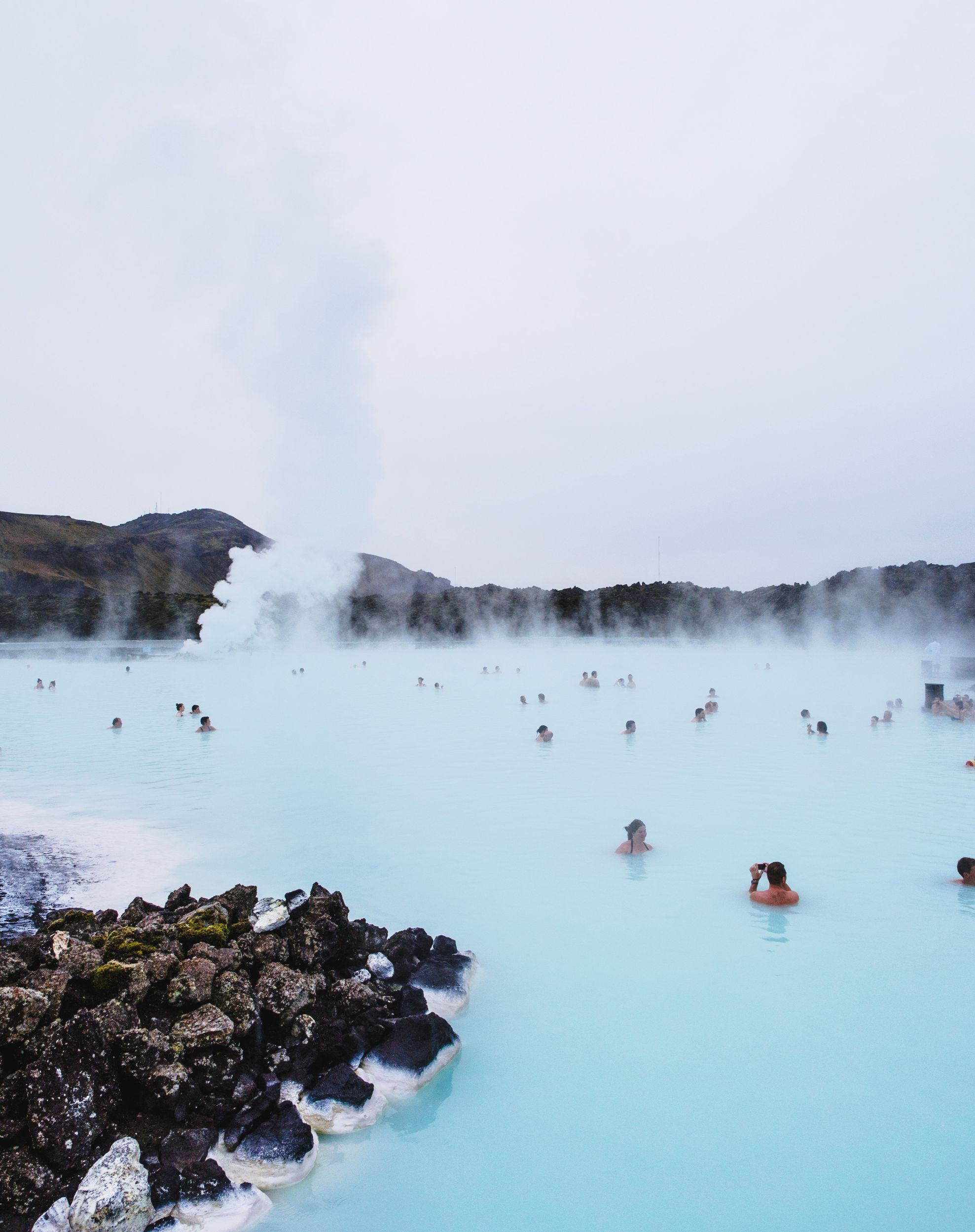 Blue lagoon with lots of people relaxing in it in the winter time in Iceland - stop in 24 hour Iceland itinerary