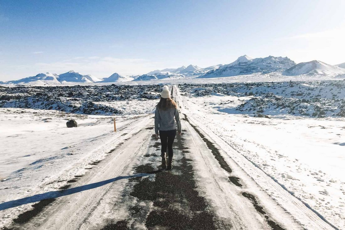 hannah walking on the road in Iceland in the winter with snow and mountains - bucket list travel