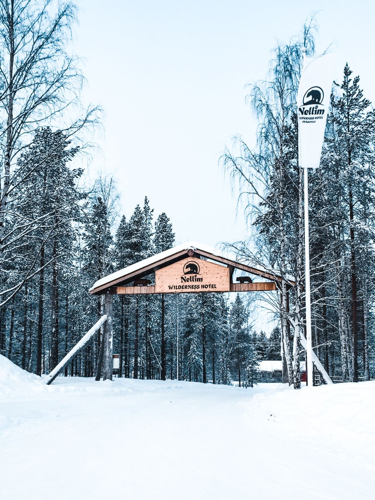 entrance to nellim wildnerness hotel in Finnish Lapland with wooden sign and flag with hotel name