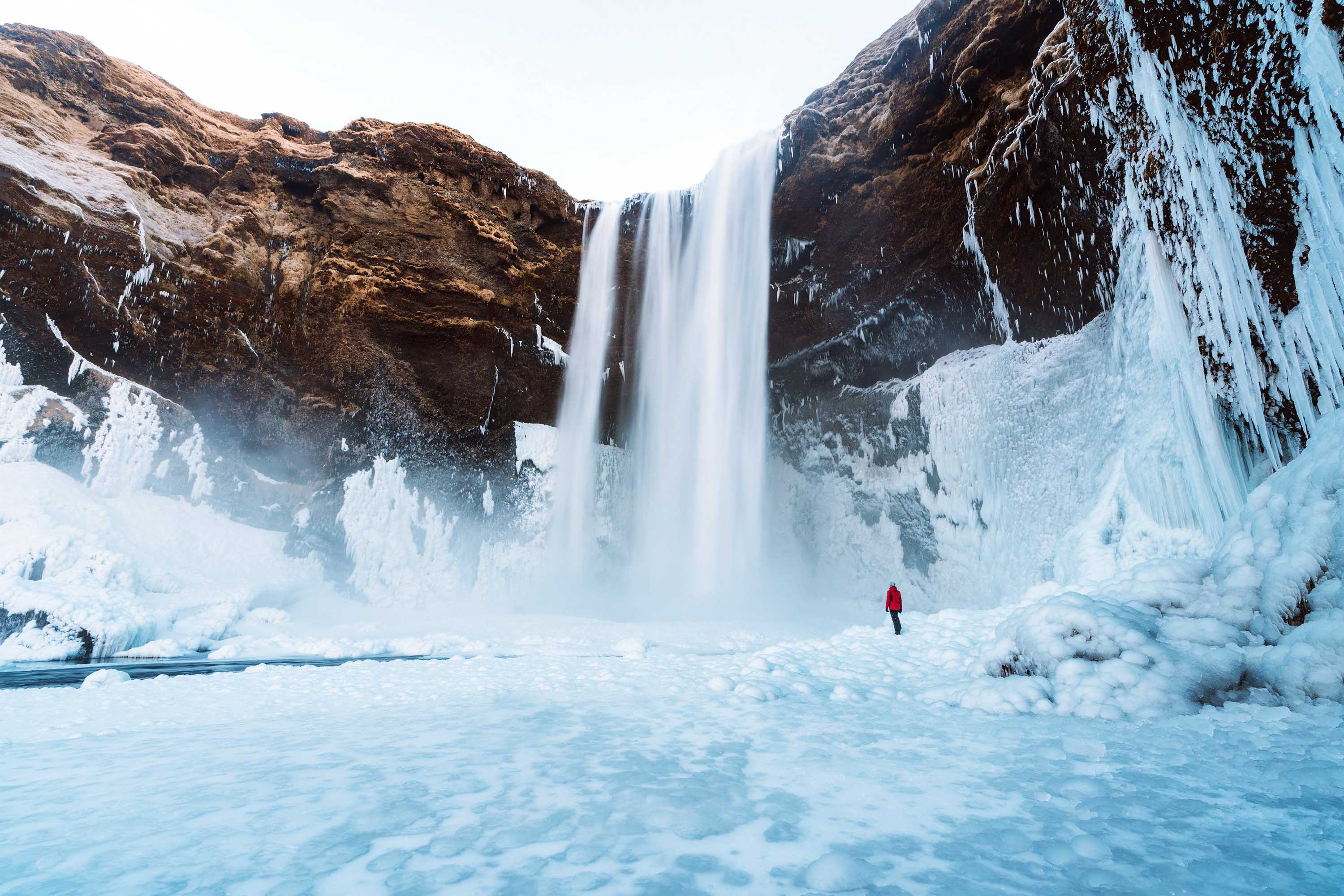 Skogafoss waterfall surrounded by ice and a single person in a red jacket standing far away near the waterfall in Iceland - major stop in 24 hour Iceland itinerary