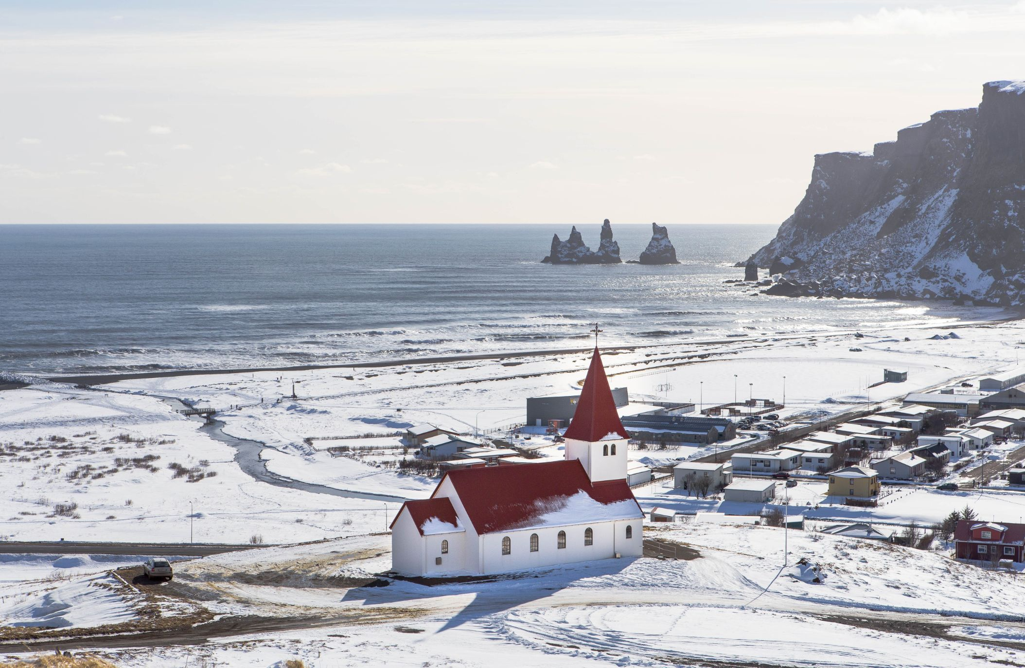 Aerial view of Vik Iceland featuring traditional Icelandic church and town of Vik with ocean in the background -  stop in 24 hour Iceland itinerary