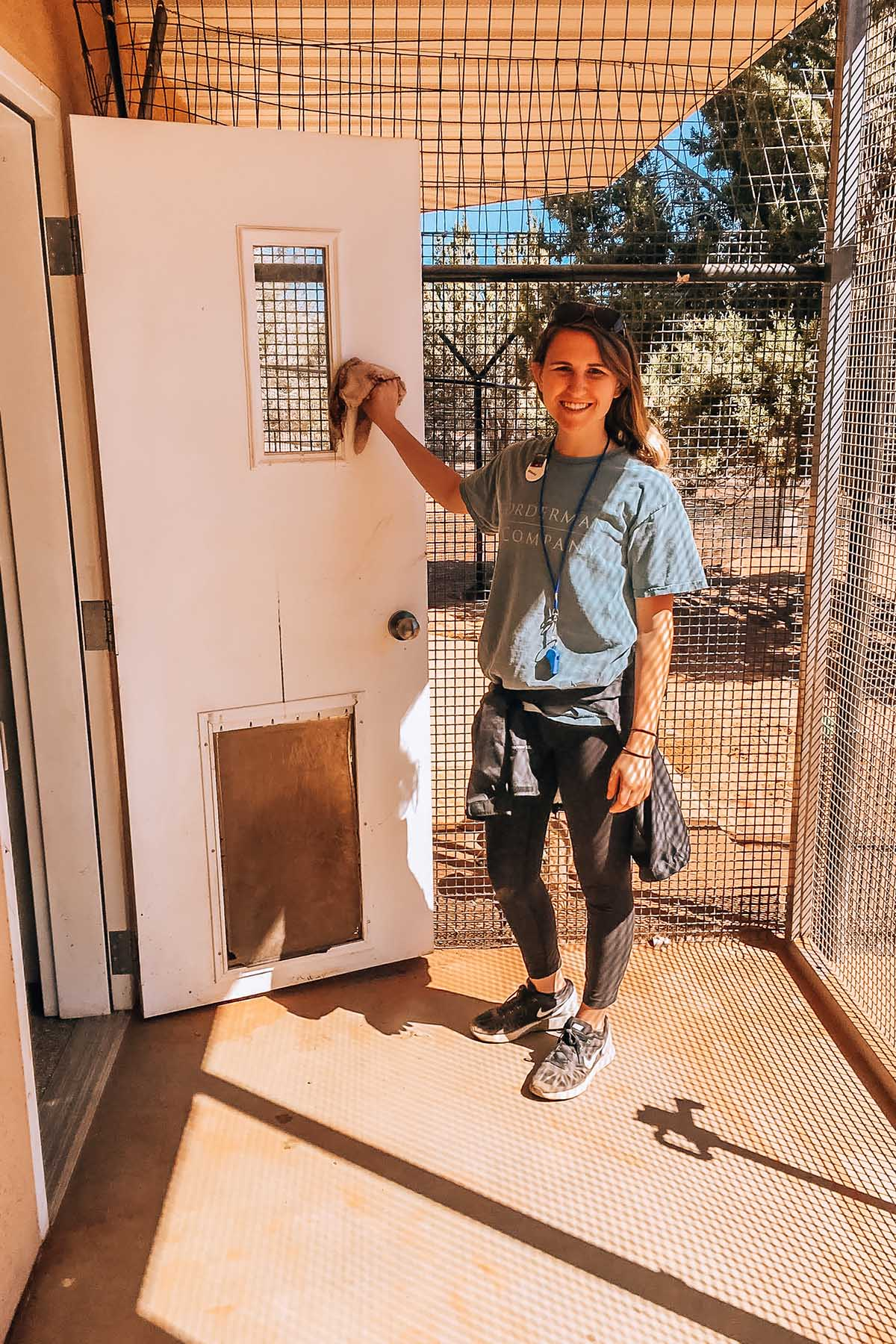 Hannah cleaning a door while volunteering at Best Friends Animal Sanctuary. She is standing and smiling towards the camera.
