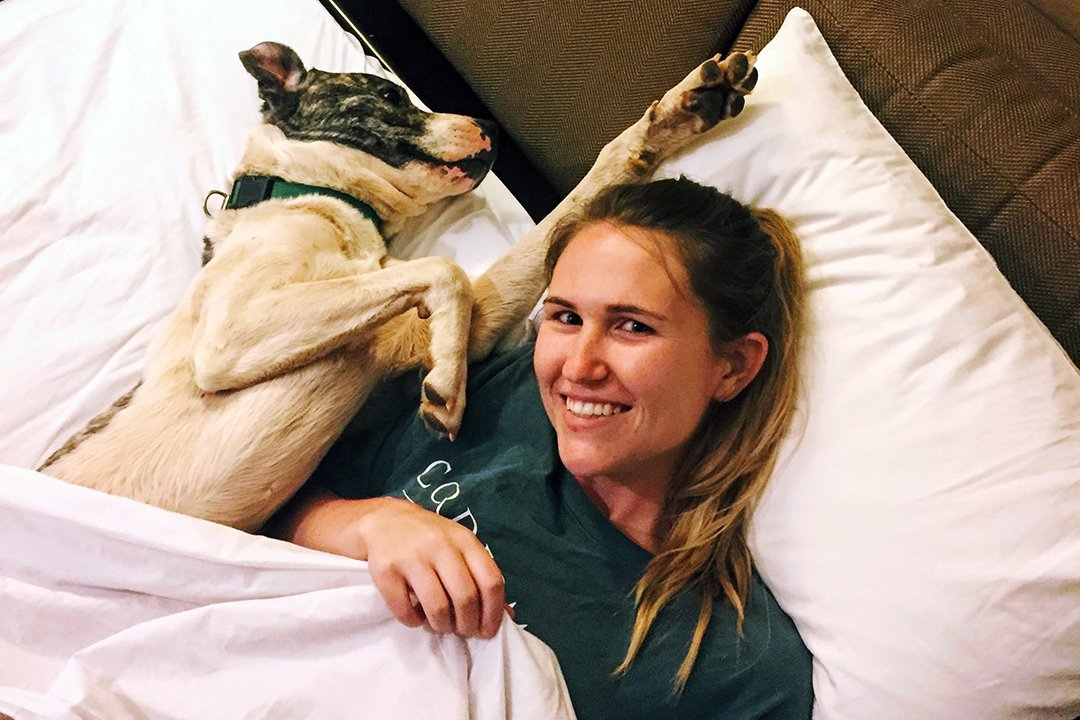 Hannah laying under covers in pull out couch at hotel while cuddling with a very happy rescue dog from Best Friends Animal Society Sanctuary