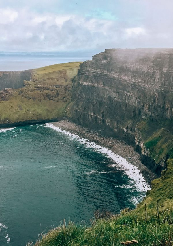view of beach and ocean below Cliffs of Moher