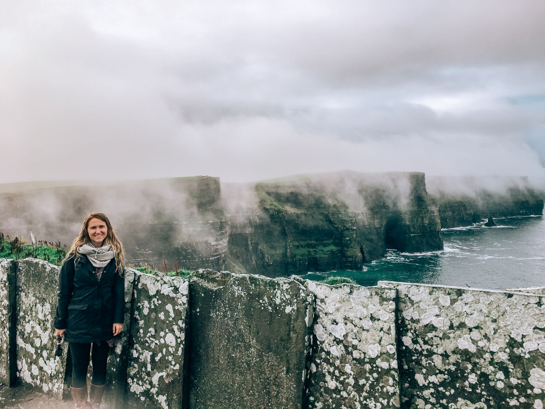Hannah standing in front of stone wall with Cliffs of Moher in background. There is fog rolling in from the left to the right of the image towards the Atlantic Ocean