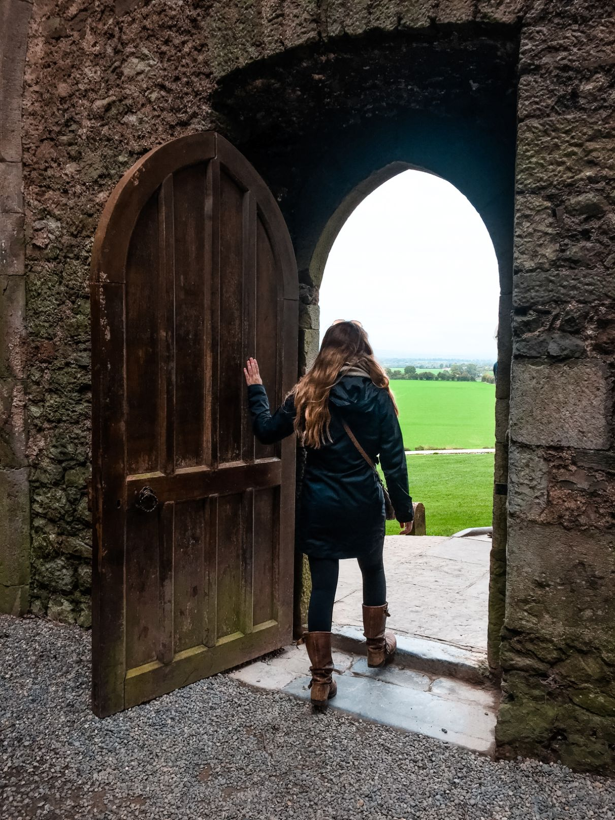 Hannah facing out of wooden doorway towards Irish countryside while visiting Rock of Cashel in Ireland