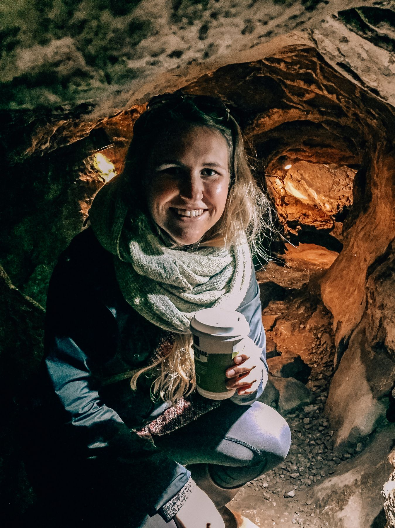 Hannah kneeling in an underground cave at Blarney castle and holding a hot chocolate