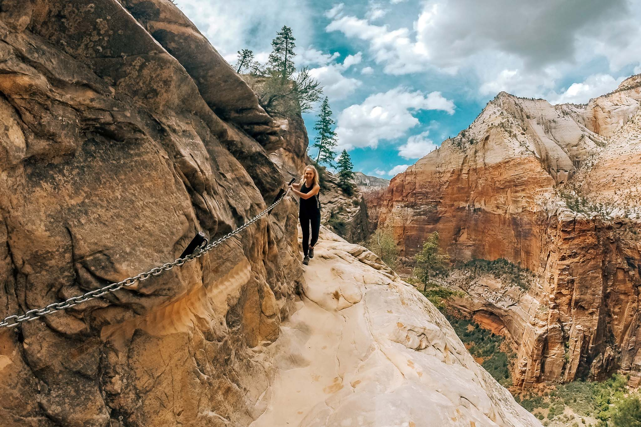 Hannah hiking at Zion National Park. She is holding onto a chain attached to the side of the mountain while overlooking a steep cliff.