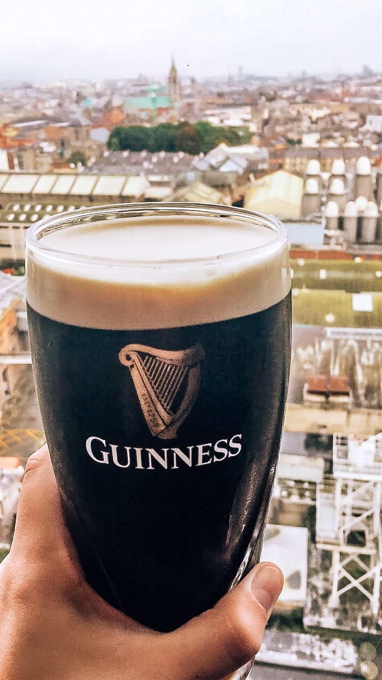 Hannah's hand holding up a glass pint of Guinness with the city of Dublin Ireland in the background