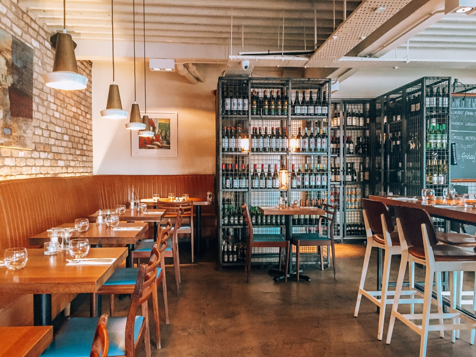 Interior of Union 8 cafe featuring wooden cafe tables lined up against the brick wall on the left with wine racks and bottles towards the back