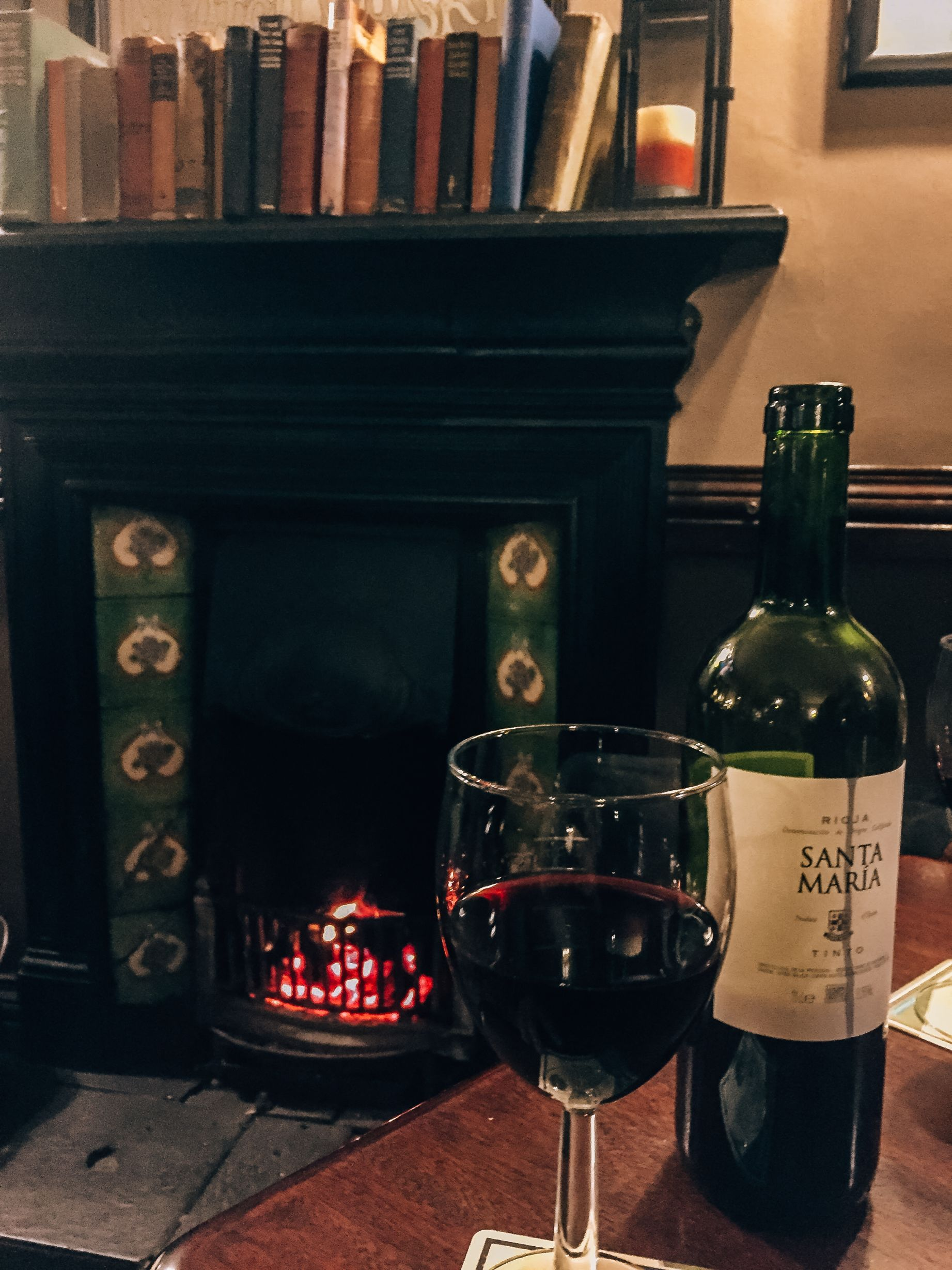 glass of wine on table next to wine bottle in front of historic fireplace in Kilrush, Ireland