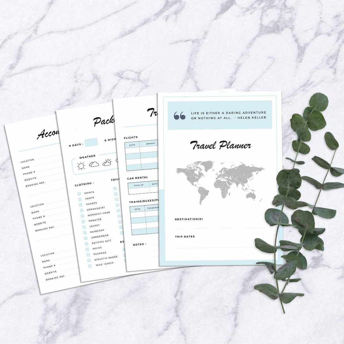 Four pages of a travel planner on a marble table next to greenery