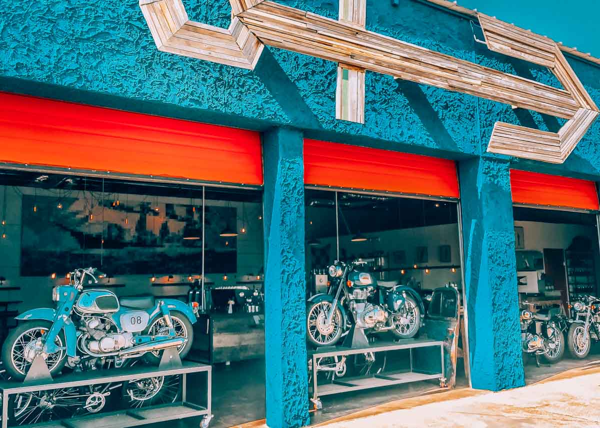 Barista Parlor coffee shop in East Nashville, Tennessee. Three garage doors are open with motorcycles and coffee shop inside