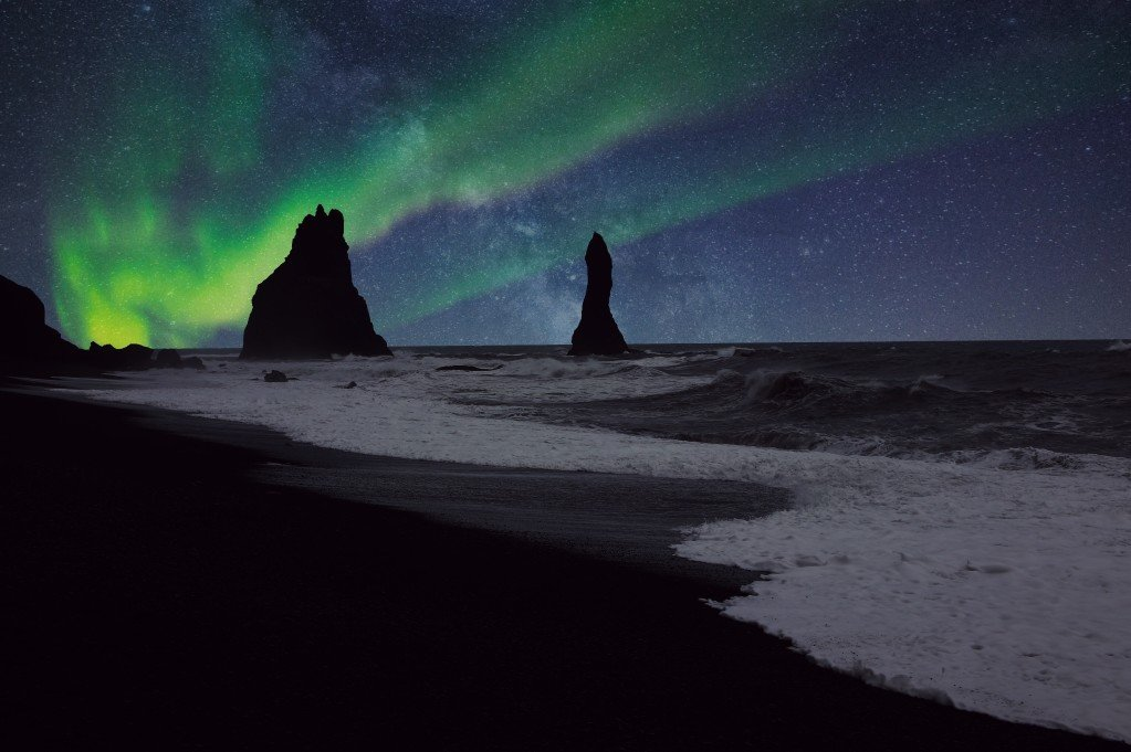 Northern lights shining over a black sand beach in Vik, Iceland