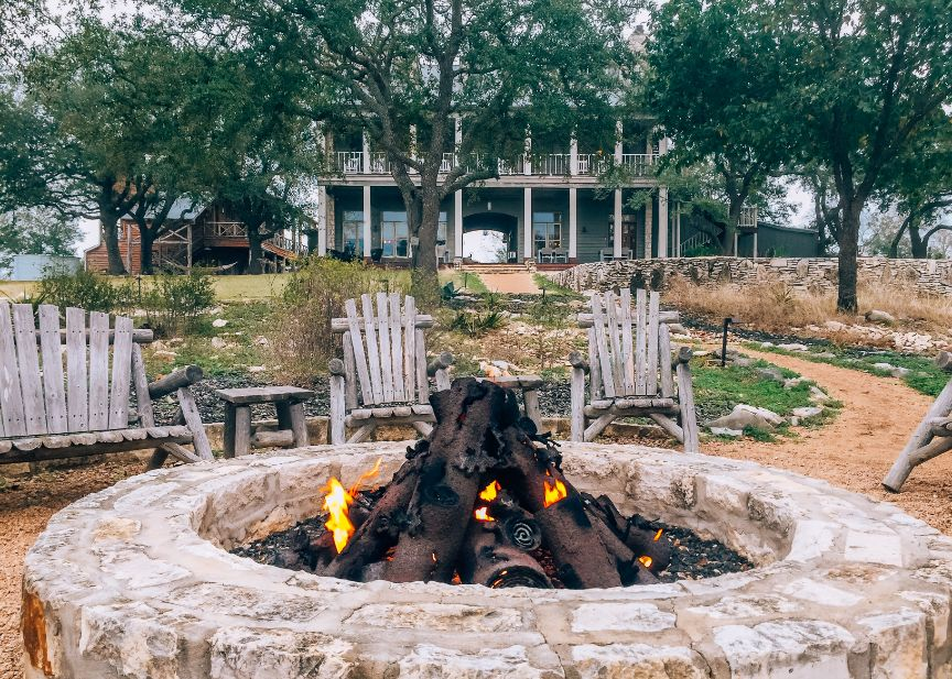 Outdoor stone fire pit with fire burning, surrounded by Adirondack chairs. Sage Hill Inn & Spa is in the background.