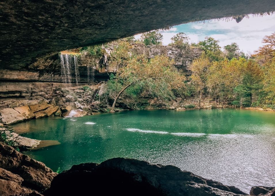 Hamilton Pool Preserve in Texas Hill Country. The photo is taken from a cavern and to the left is a waterfall while the center of the image has a blue pond. There are trees framing the pond.