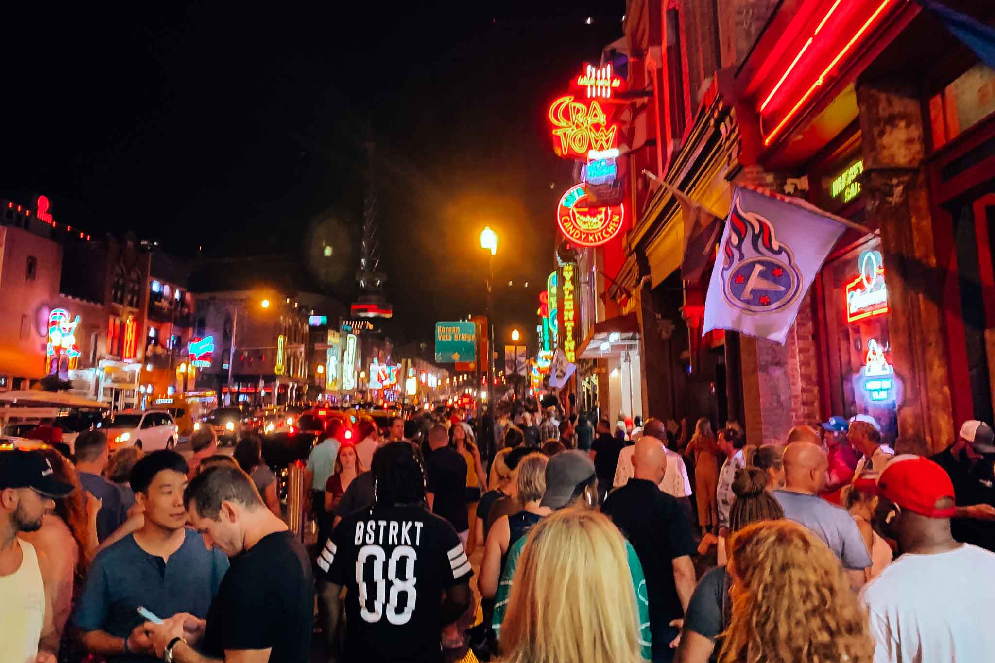 Nashville street at night filled with people walking to bars