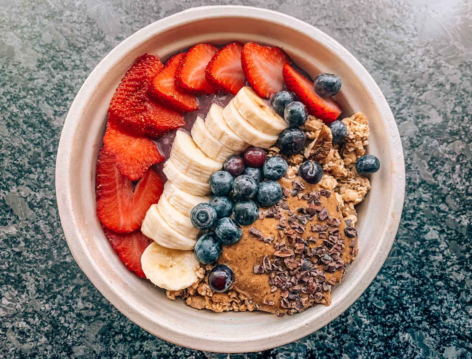 Acai bowl with strawberries, blueberries, banana, peanut butter, and granola at The Juicery in Portsmouth New Hampshire