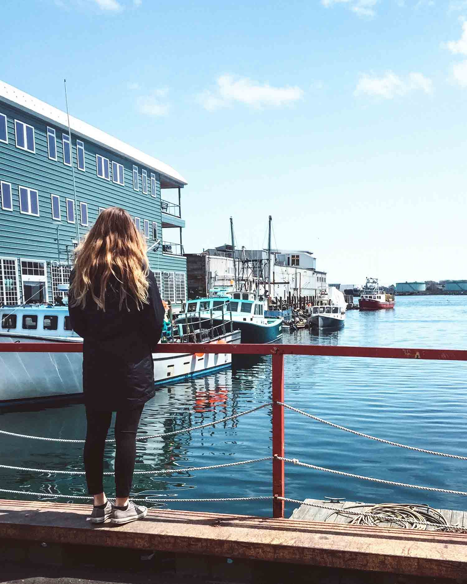 Hannah Corderman standing on the edge of the waterfront in Portland Maine looking out at boats in the water