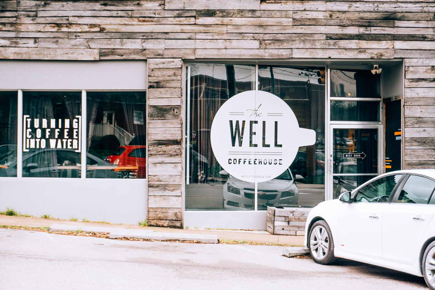 exterior of Well Coffeehouse with circular window graphic that features the company name. To the left is another window graphic that says Turning Coffee into Water
