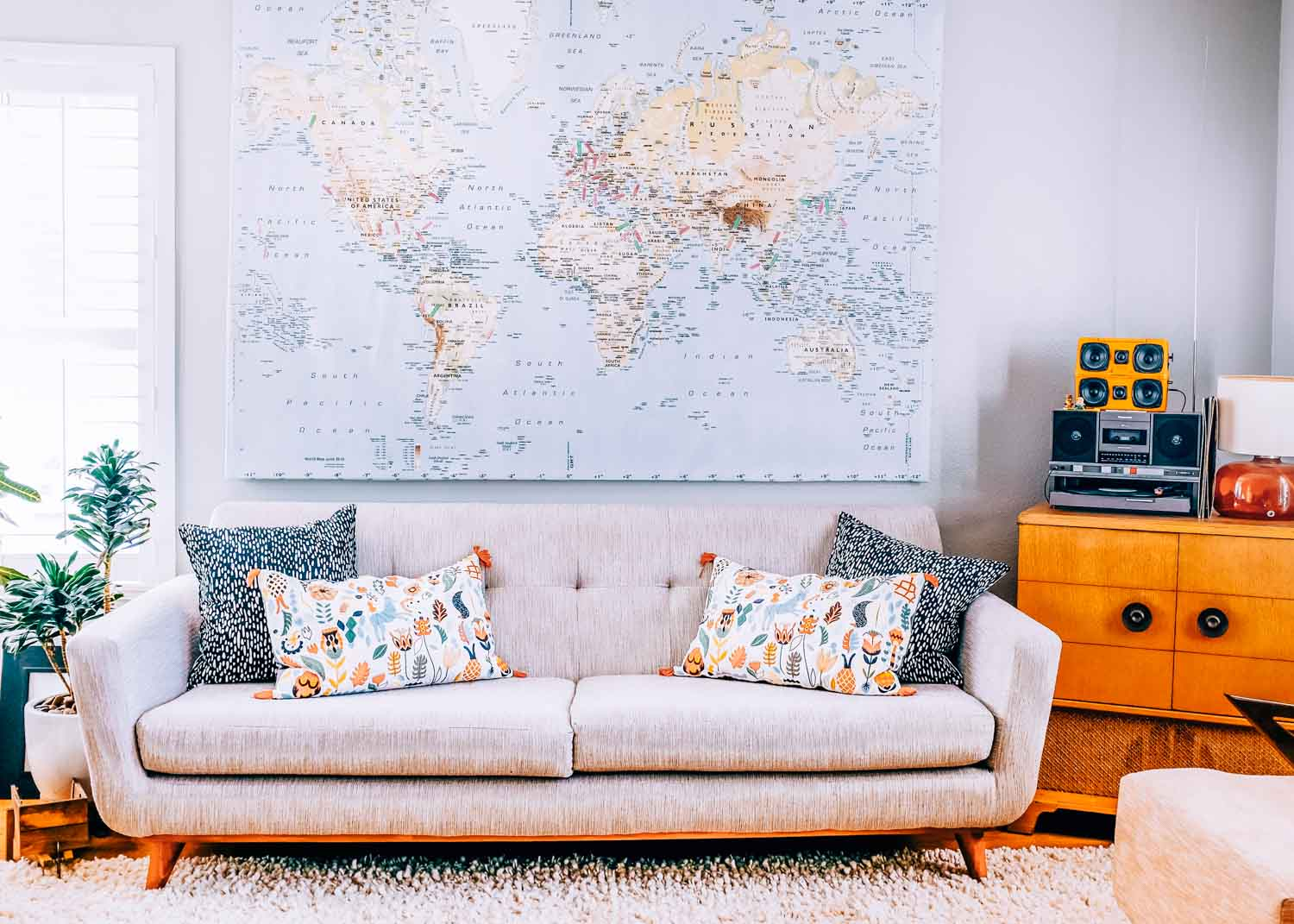 Modern living room couch with world map on wall. To the right is a stereo on top of a wooden console table.