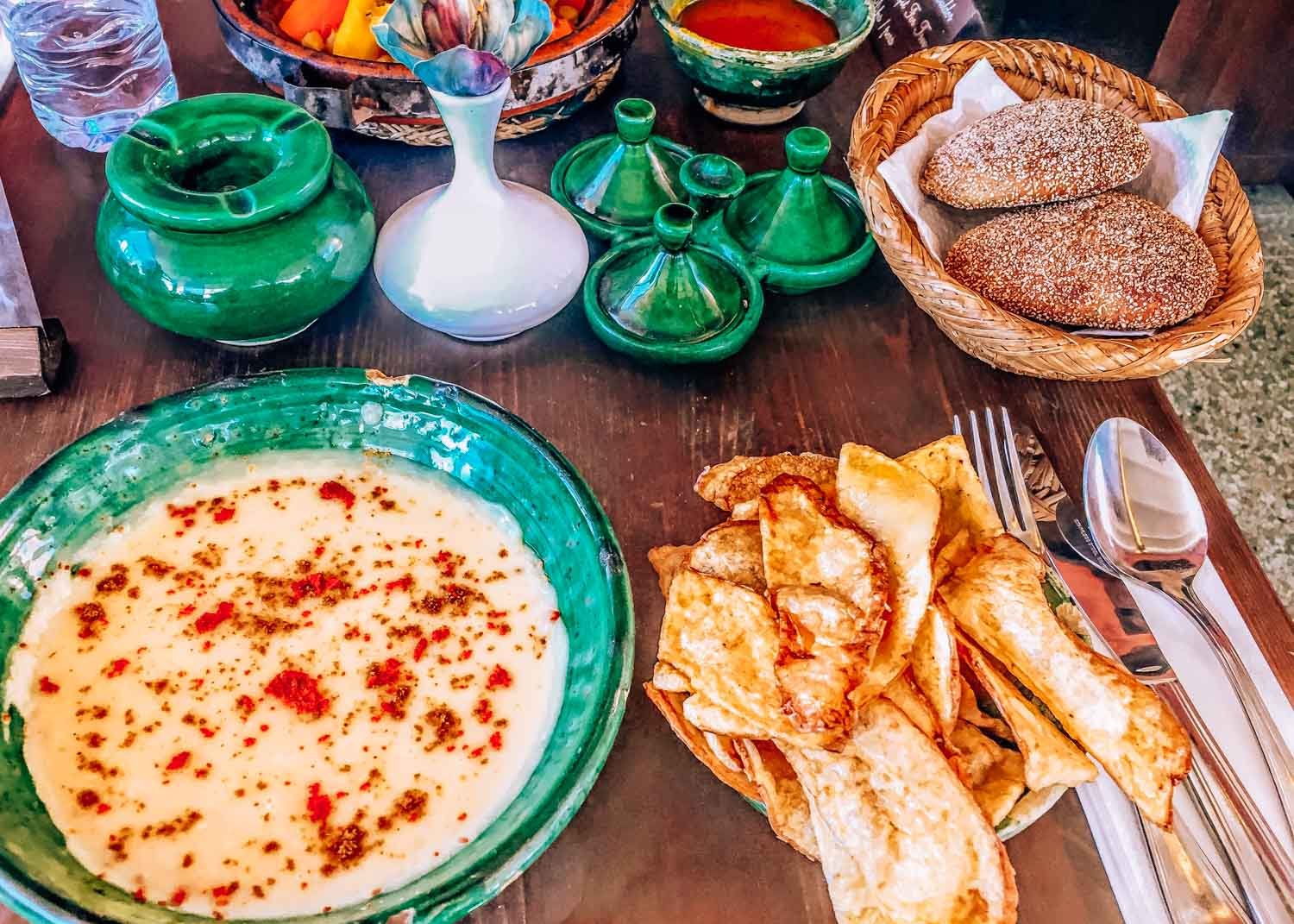Moroccan food, including soup and bread, on a table.
