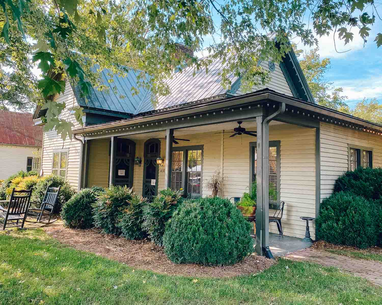 Historic home turned restaurant called 1892 in Leiper's Fork, Tennessee. There is one porch light on and a couple rocking chairs in the yard.
