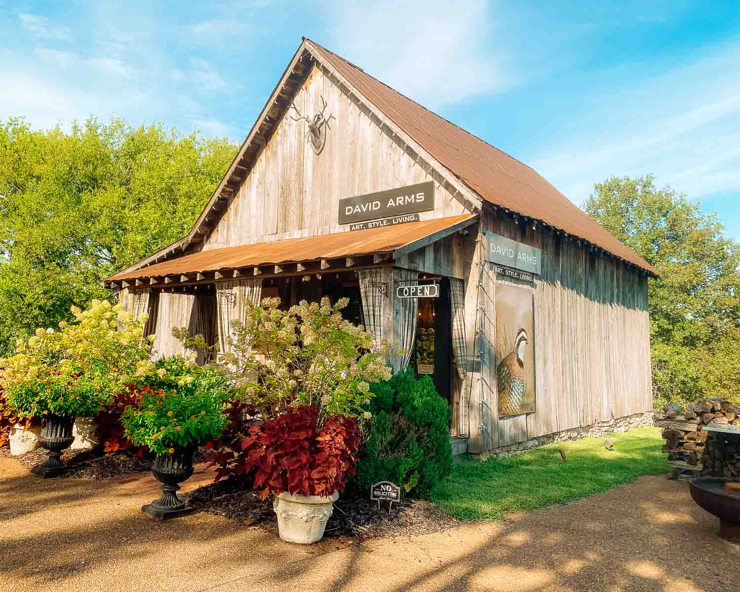 Exterior of David Arms Gallery, a barn surrounded by potted plants, well-trimmed grass, and a pebbled driveway.