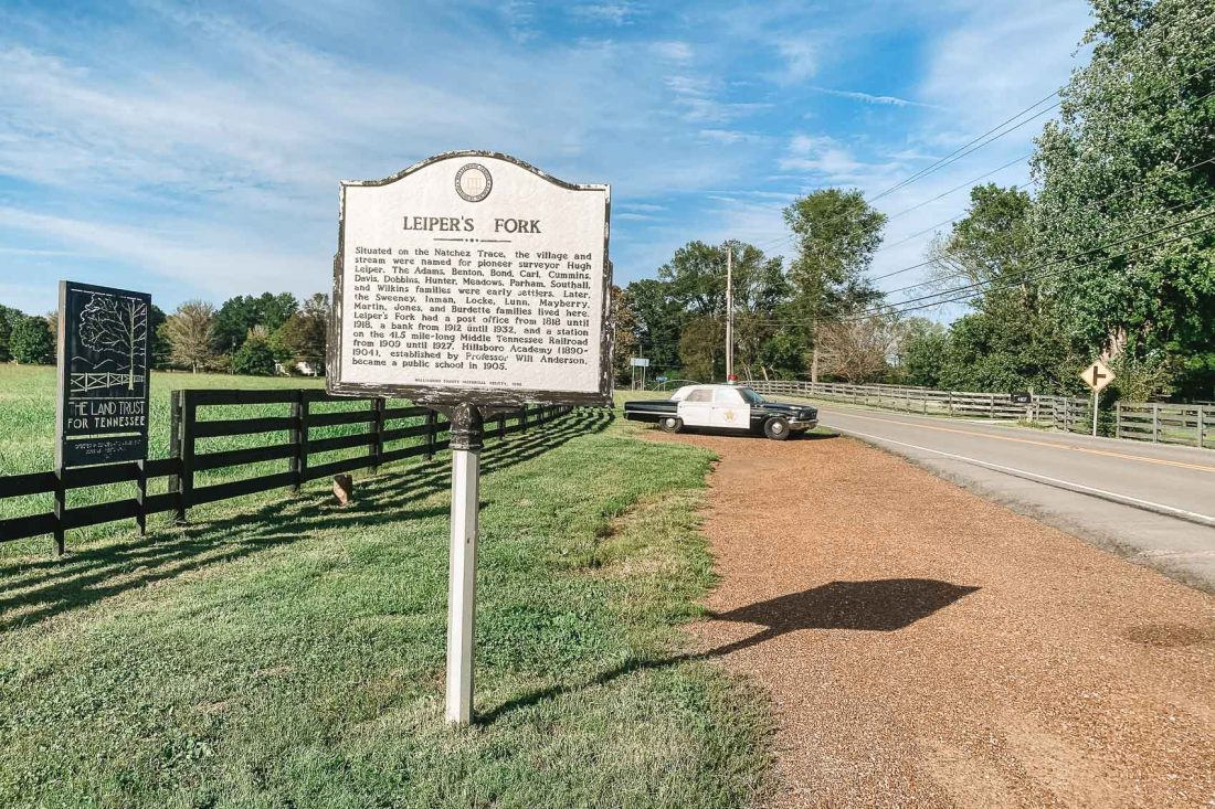 town sign of Leipers Fork tennesee with old fashioned cop car in the background. A farm is to the left and a road is to the right - bucket list travel things to do in Leipers Fork