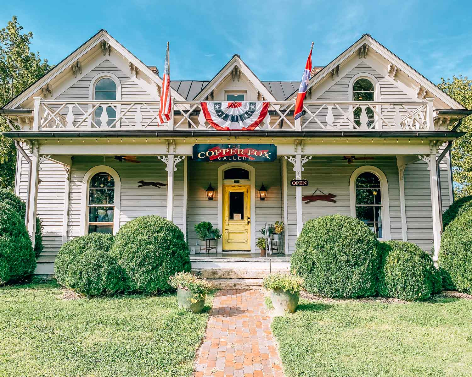 Historic southern home that is now the Copper Fox Gallery in Leiper's Fork, Tennessee. There is an American flag and Tennessee state flag hanging from the upstairs balcony.