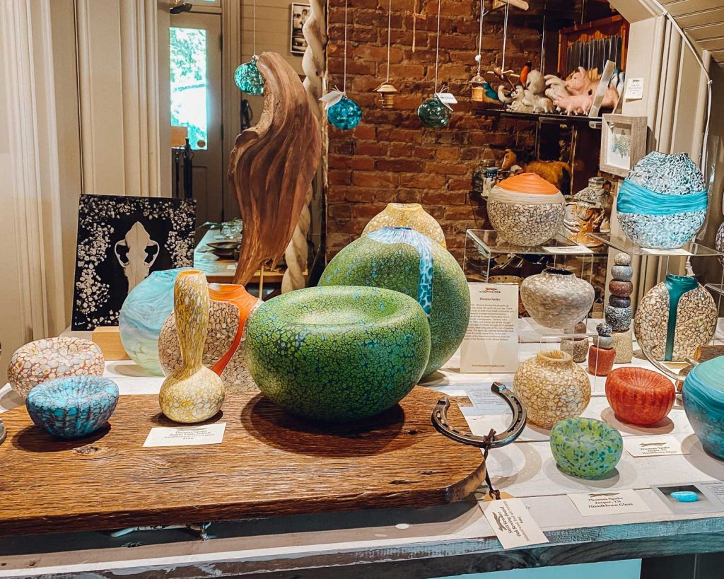 An assortment of colored glass-blown art pieces sitting on a table at Copper Fox Gallery.