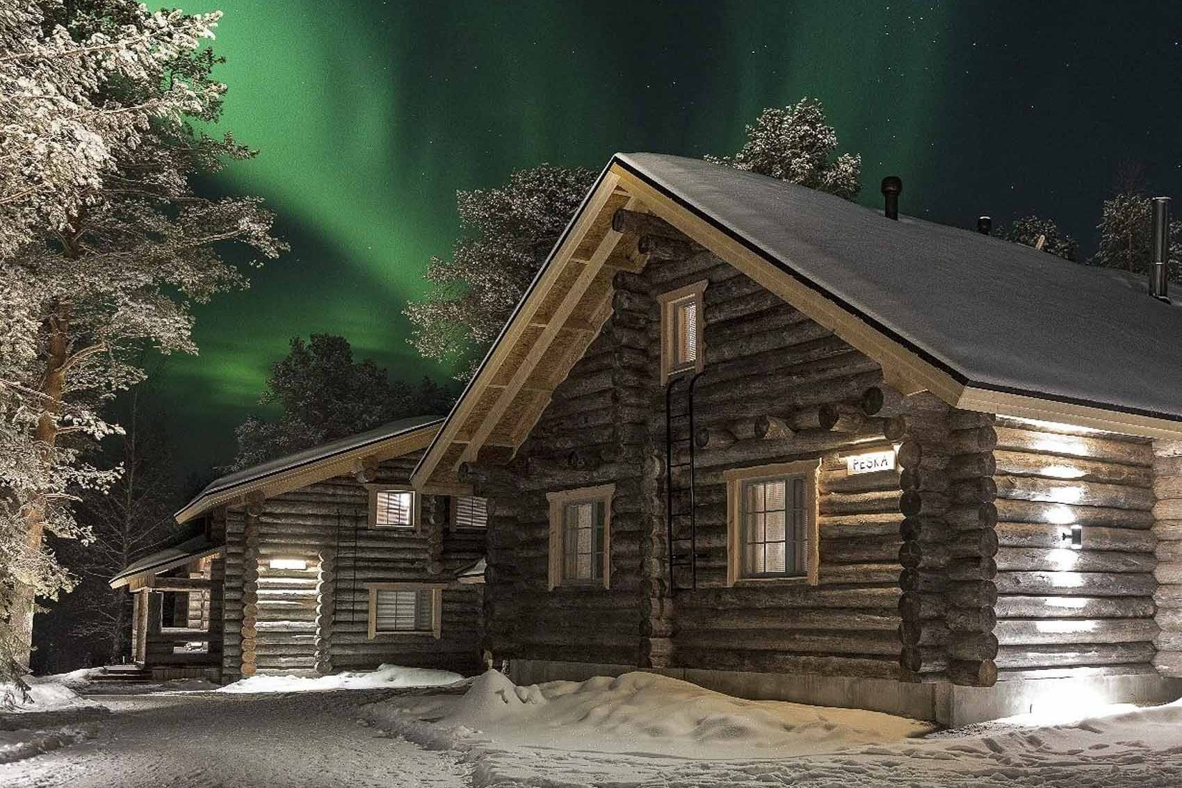 wilderness lodge in Finnish Lapland with northern lights in the background - bucket list travel
