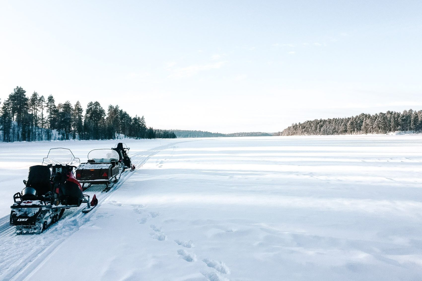 snowmobile on snow covered frozen lake in Finnish Lapland near Russian border - bucket list travel