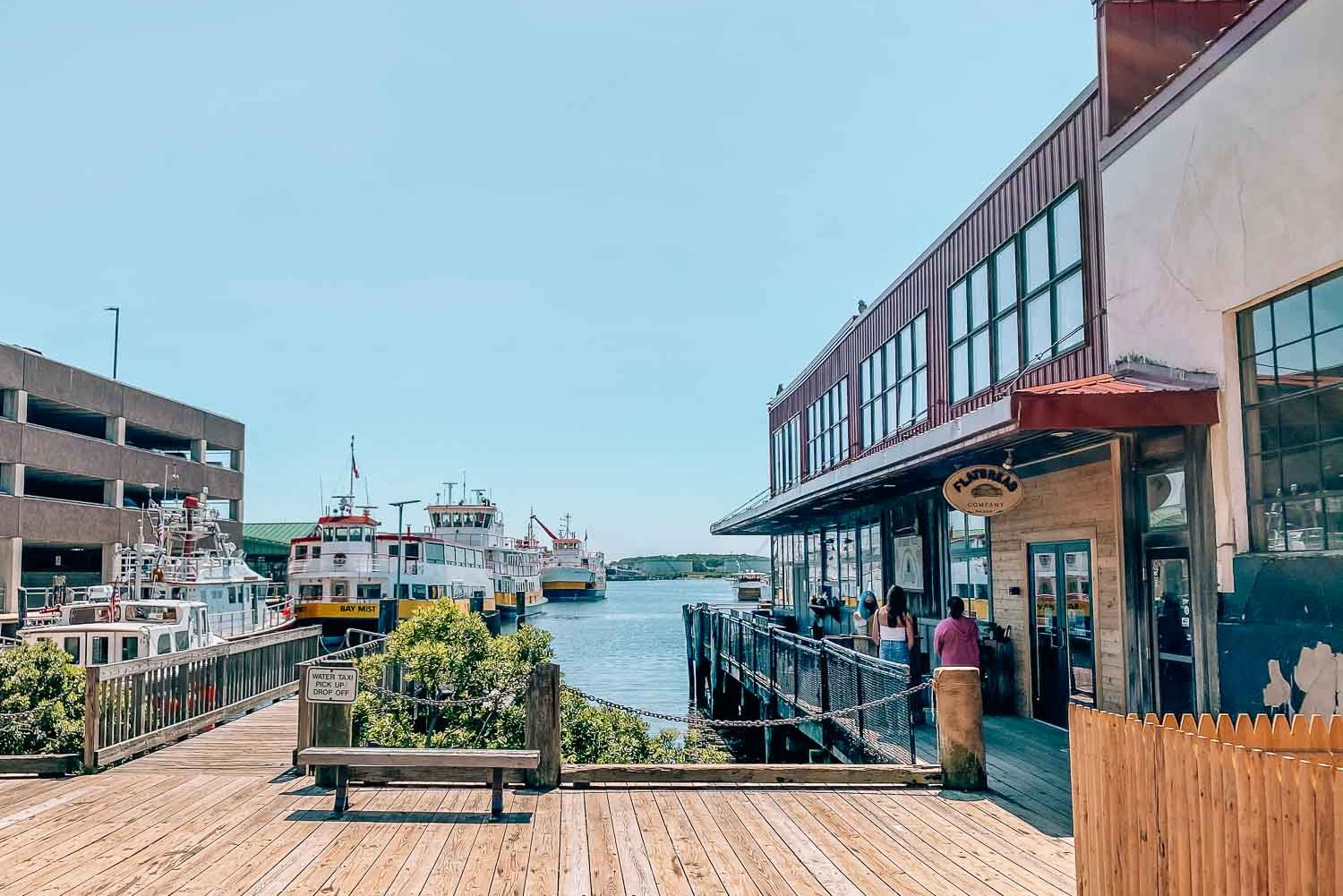 exterior of Flatbread Company pizza restaurant in Portland Maine. There is a boardwalk that surrounds the building that is waterfront. In the harbor there are a few large boats.