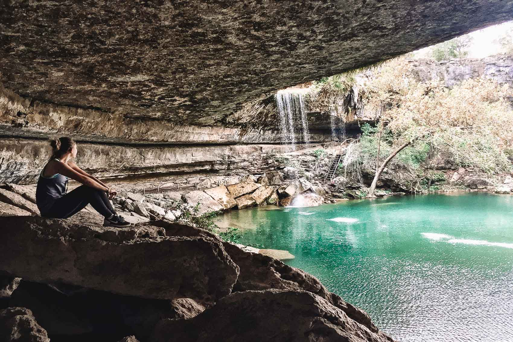 hannah sitting on rock looking at hamilton pool in texas hill country