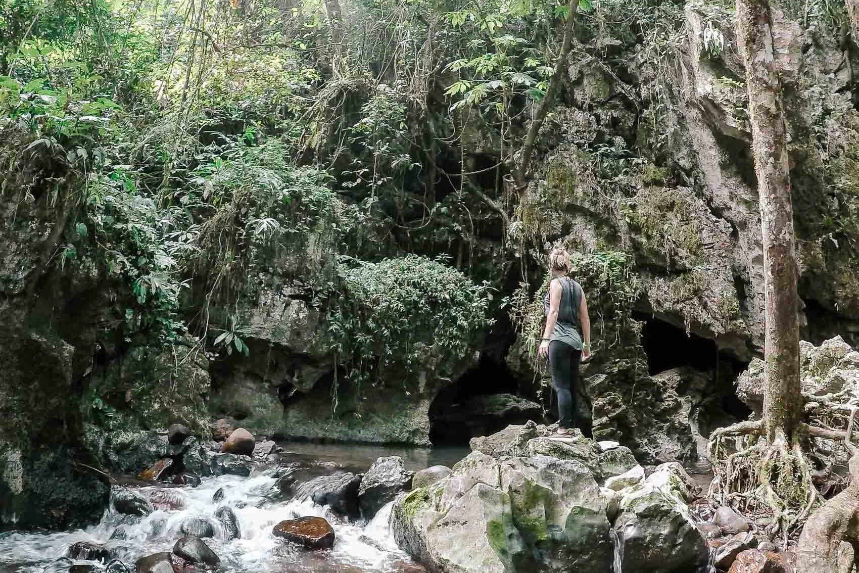Hannah standing on rocks near a waterfall and cave in Khao Sok National Park in Thailand
